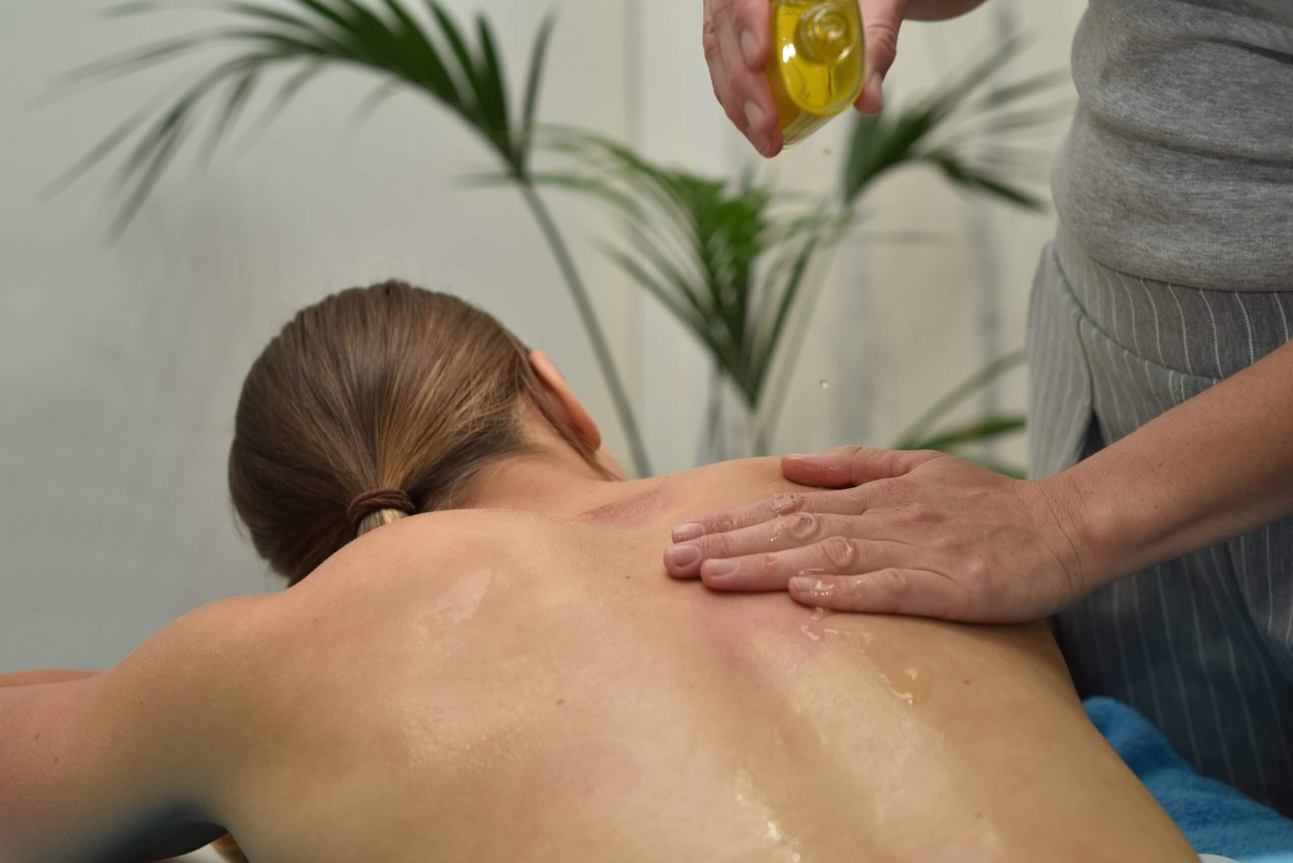 Sara bereitet die Haut mit Öl für die Klassische Massage vor