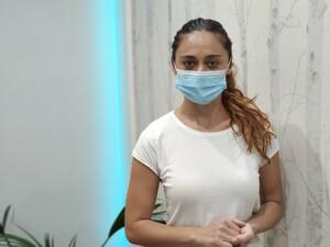 Sara mit Mund-Nasen-Schutz verweist auf die Hygiene-Vorschriften